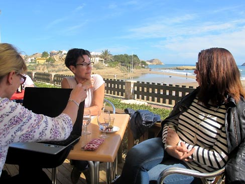 Spain: Writers sharing some work at a local beach cafe